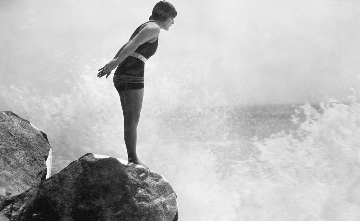 Photo noir et blanc d'une femme sur un rocher qui va plonger dans la mer