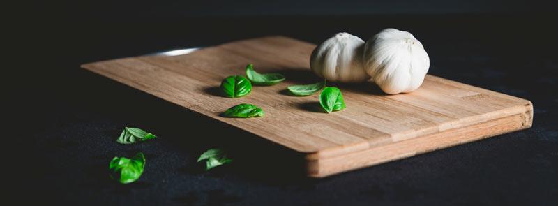 Photographie sur fond noir d'une planche à découper en bois avec une gousse d'ail et quelques feuilles de basilic
