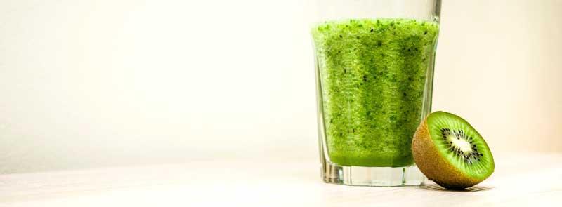 Photographie d'un demi-kiwi cru et d'un verre de smoothie au kiwi