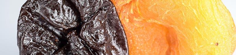 Gros plan photographique d'un pruneaux séché et d'un abricot secs, aliments riches en fibres alimentaires