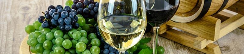 Photographie d'un verre de vin rouge et d'un verre de vin blanc devant une grappe de raisins rouges et blancs et un petit tonneau en bois, pour illustrer le fait que le vin est une boisson riche en fer.