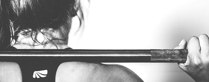 Photographie en noir et blanc du dos et de la nuque d'une femme en tenue de sport en train de lever une barre de musculation pour perdre du poids