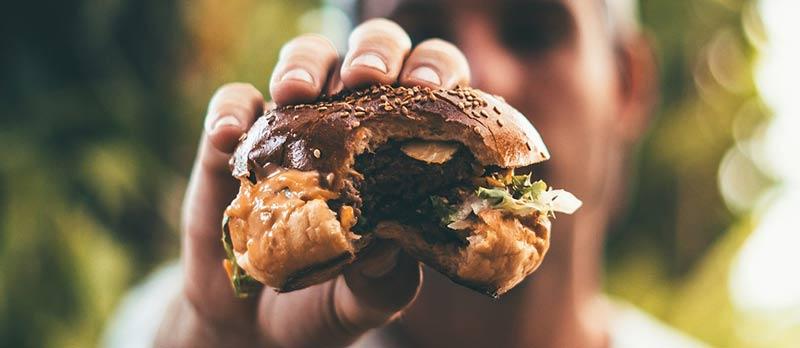 Homme tenant dans sa main un hamburger déjà croqué ne parvenant pas à perdre du poids