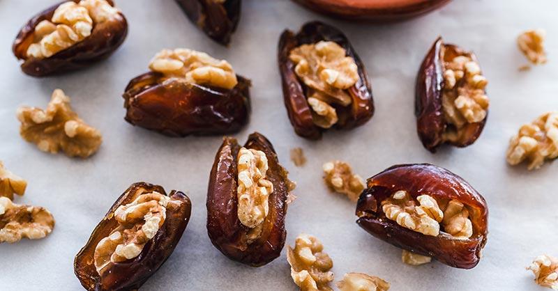 Photographie de noix insérées dans des dattes fendues en deux, parfaites pour faire un encas qualtitatif en cas d'envie de grignotage.