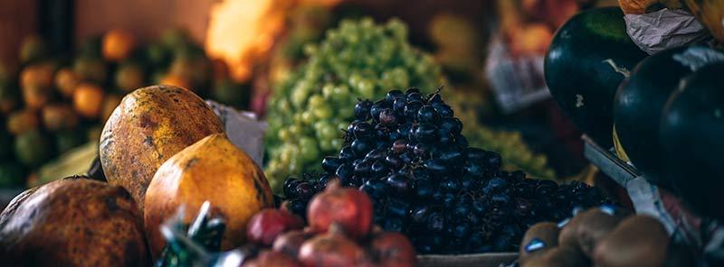 Aliments bio : assortiment de fruits sur l'étal d'un marchand en gros plan.