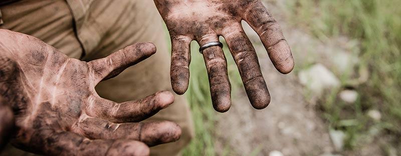 Photographie des deux mains d'un paysans recouvertes de terre après avoir cultivé des aliments bio