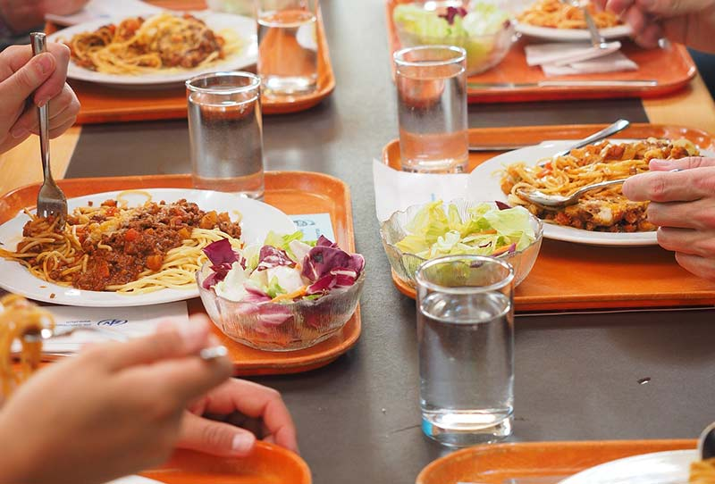 Photographie d'une table avec plusieurs plateaux oranges de self contenant des assiettes de spaghettis bolognaise, une salade vert et un vert d'eau. Les convives sont en train de manger un repas de midi typique des cantines scolaires et de la restauration collective.