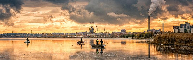 Photographie d'hommes en train de pêcher à la ligne sur de petites barques dans un étang pollué au soleil couchant. Cet environnement ne permet pas de produire des aliments bio en raison de la proximité de la ville et des nombreuses industries, à l'image de la cheminée d'un incinérateur qui crache dans le ciel un panache de fumée menaçant.
