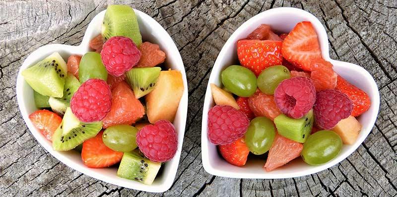 Photographie couleur de deux bols blancs en forme de cœur contenant des fruits frais bourrés de vitamine, posés sur une table en bois brut.