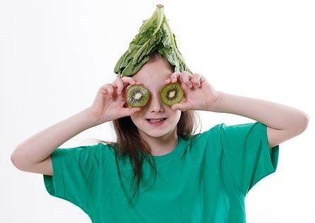 Manipulation de légumes par les enfants : Photographie d'une fille avec un tshirt vert qui a placé des feuilles de chou sur sa tête et deux tranches de kiwi sur ses yeux.