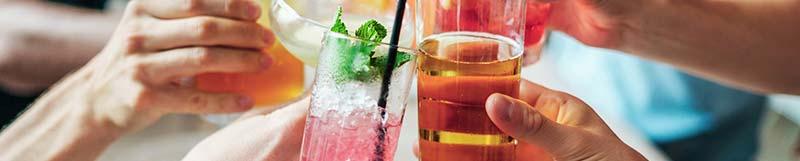 L'alcool est l'une des première cause de cirrhose du foie, avec le sucre, la graisse et la malbouffe en général (qui causent la maladie du soda— NASH) : photographie d'une bande d'ami trinquant avec des verres d'alcool colorés et des cocktails de fruits à l'apéro.