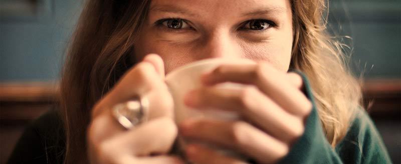 Photographie en gros plan du visage d'une femme buvant une tasse de café