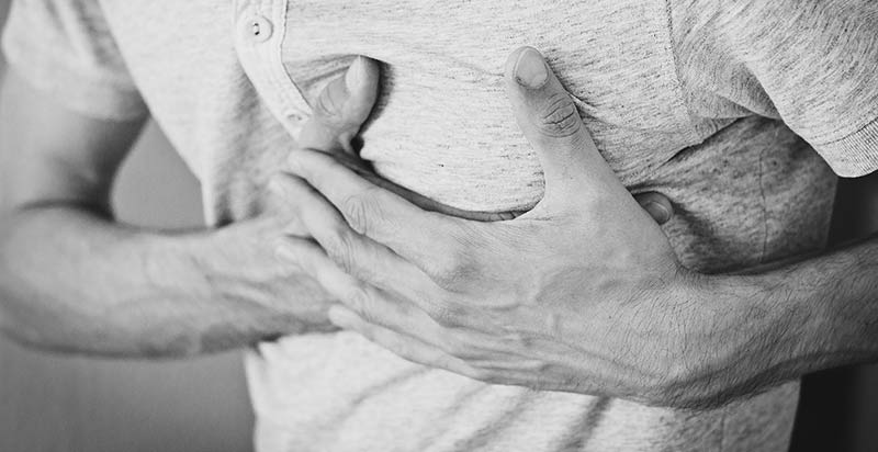 Photographie en gros plan et en noir et blanc du thorax d'un homme se tenant le cœur en raison d'une maladie cardiaque