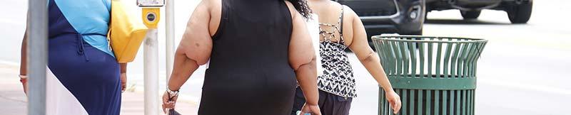 Photographie de femmes américaines obèses marchant dans la rue. L'obésité est l'une des causes de la maladie du soda (foie gras humain), ou NASH - cirrhose non alcoolique.