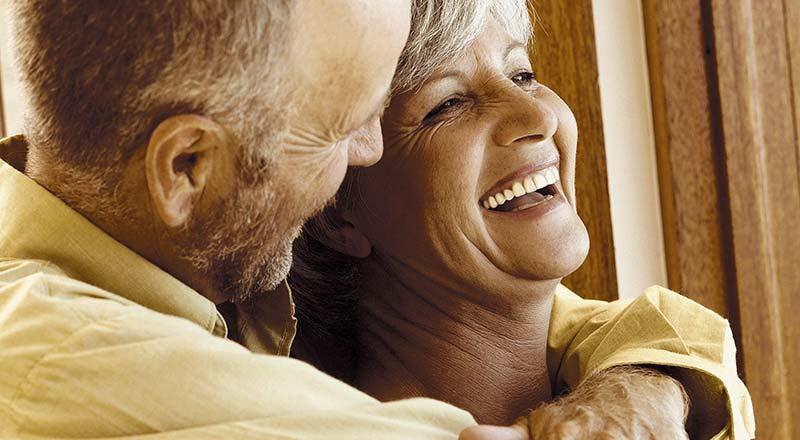 Photographie en teinte sépia d'un couple de senior enlaçés et heureux, souriants à pleine dents, joyeux d'avoir réussi à se débarrasser de l'arthrose et à ne plus avoir de douleurs dans leurs articulations grâce à des recettes simples, naturelles et sans effets secondaires.