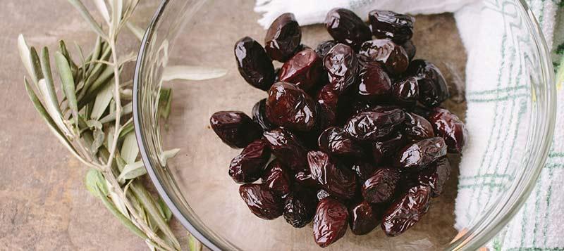 Bols d'olives noire posé sur une table dans un saladier en verre