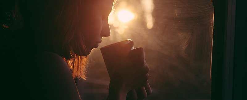 Femme en contre-jour buvant un thé chaud devant sa fenêtre : attention aux risques de carences en fer.