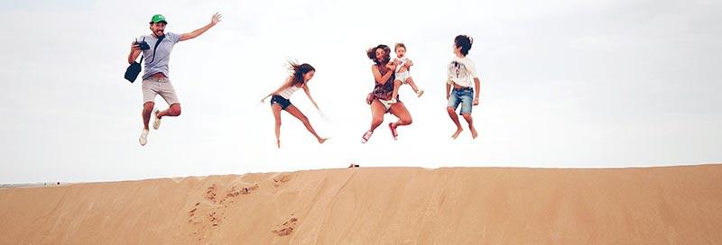 Micronutrition : famille heureuse qui saute au sommet d'une dune de sable pour montrer son bonheur et sa bonne santé.