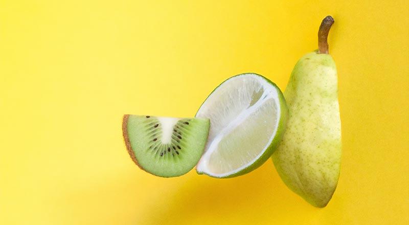 Photographie de trois fruits (kiwi, citron, poire) découpés sur un fond jaune pour illustrer le fait que les micronutriments sont essentiels à la santé et à la micronutrition.