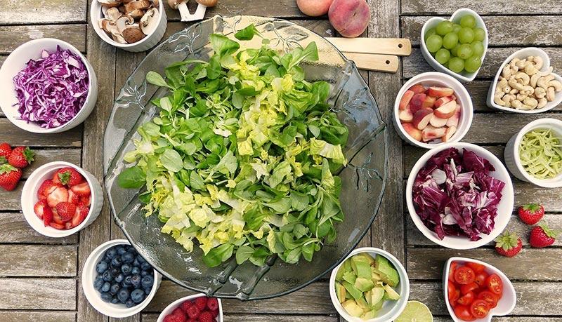 Micronutriments : photographie d'une salade verte dans un saladier entouré de petits bols contenant une grande variété des fruits et légumes frais et crus, framboise, fraise, betterave, raisin, champignons, chou rouge, fraise, myrtilles, pêche, avocat, citron.