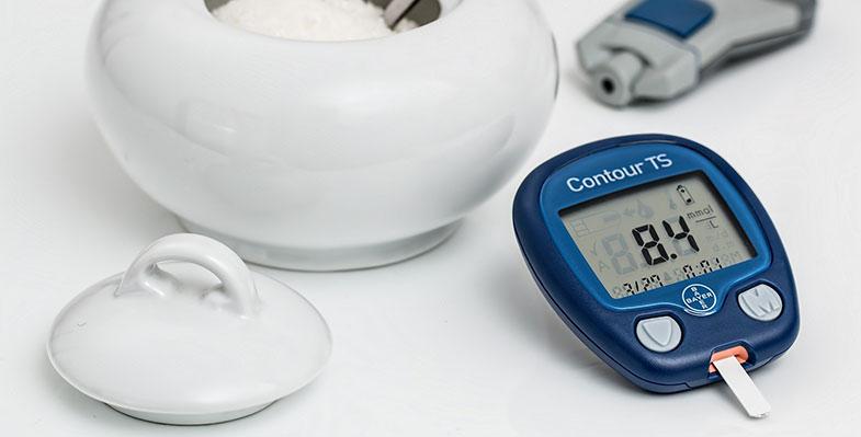 Diabète : Photographie d'un appareil de mesure de la glycémie devant un pot de sucre en poudre, afin d'illustrer les enjeux du diabète.